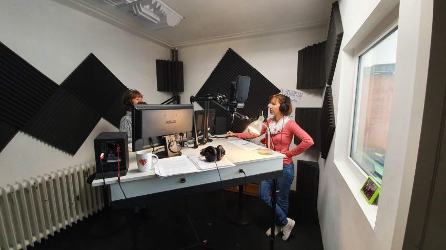 Zwei Frauen stehen in einem Ton-Aufnahmestudio. Sie haben Kopfhörer auf und sprechen in Mikrofone.